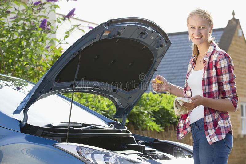 Woman Checking Oil Level In Car Engine stock image