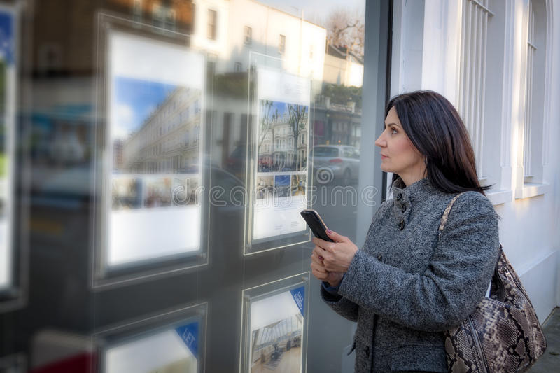 Woman checking the real estate listings. Mature woman wearing a grey coat and a purse is looking at the ads in the window of a real estate agency for a new place royalty free stock images