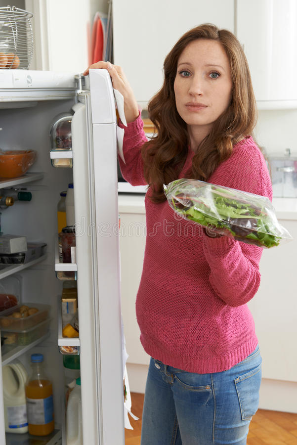 Woman Checking Sell By Date On Salad Bag In Refrigerator. Woman Checks Sell By Date On Salad Bag In Refrigerator stock image