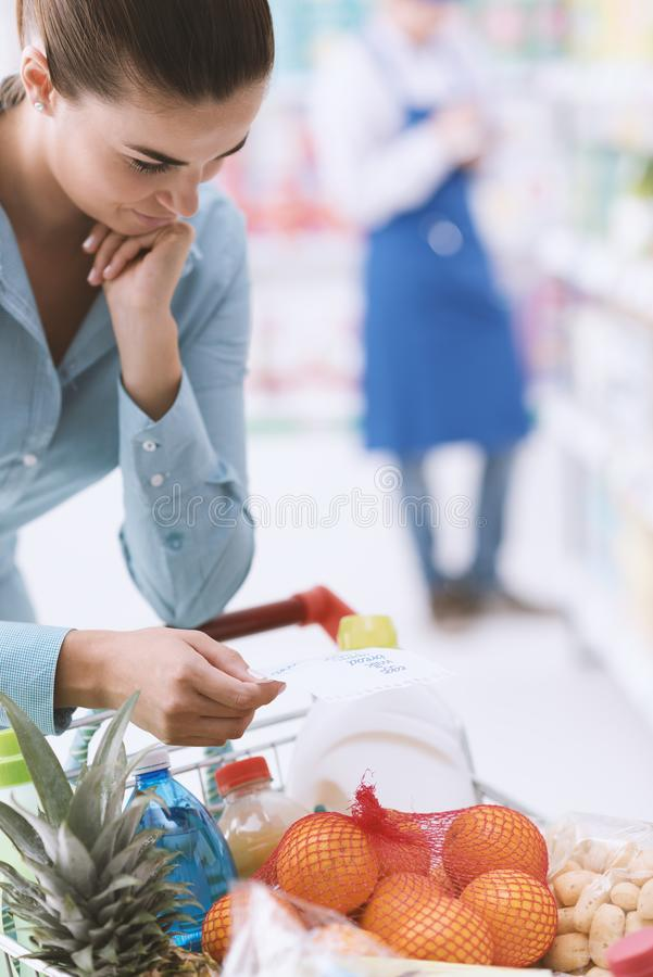 Woman checking a shopping list. Woman doing grocery shopping at the supermarket, she is pushing a full shopping cart and checking a list royalty free stock photography