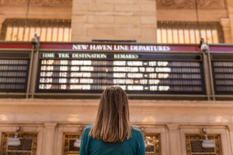 Woman checking the train timetable in the grand central terminal in new york stock image