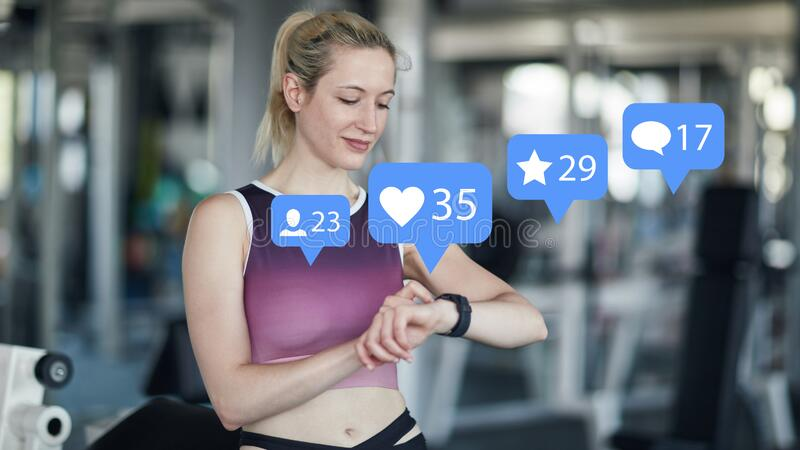 Woman checks social media channels at the fitness center. Woman checking social media channels in fitness center on her smart watch royalty free stock photos
