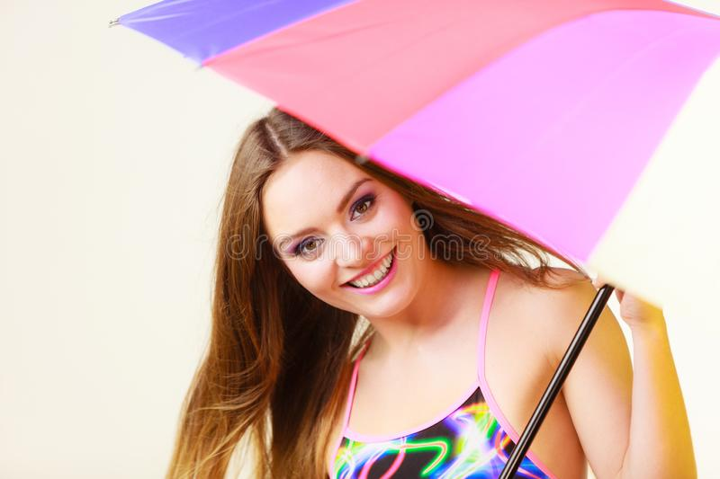 Woman standing under colorful rainbow umbrella royalty free stock photography