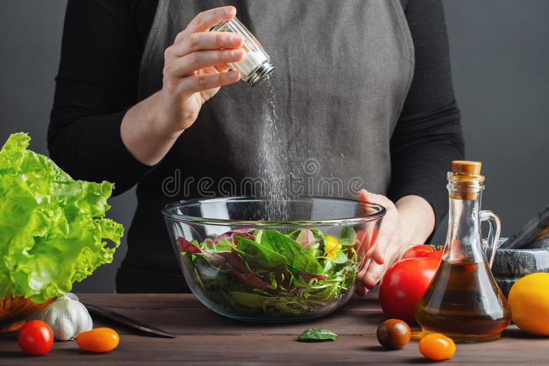 Woman chef in the kitchen preparing vegetable salad. Healthy Eating. Diet Concept. A Healthy Way Of Life. To Cook At Home. For royalty free stock images