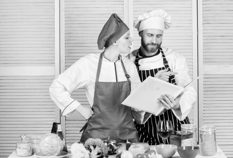 Woman chef and man cooking food together. Culinary family concept. Couple in love cooking healthy recipe. Amateur cook royalty free stock images