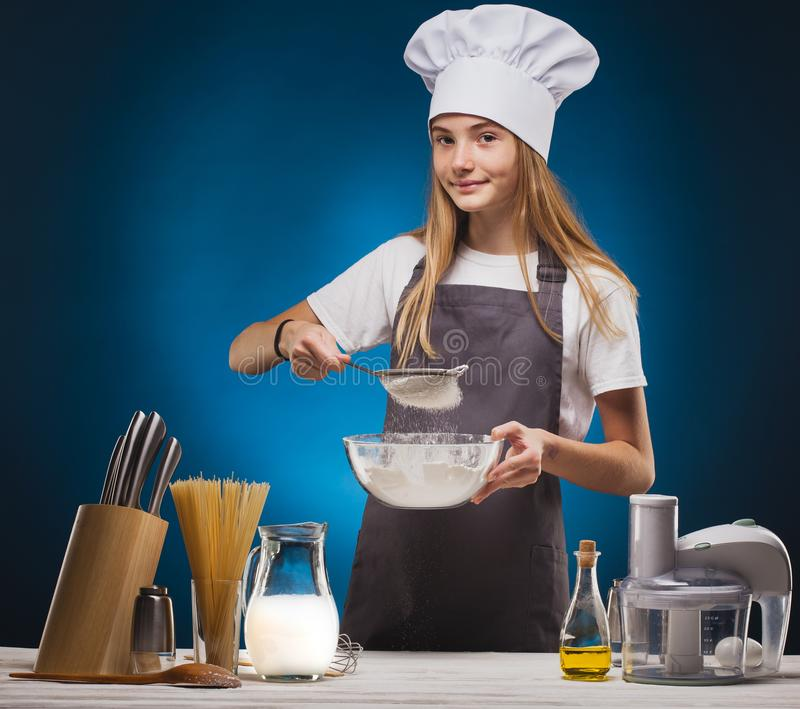 Woman Chef prepares a delicious dish on a blue background. stock photography