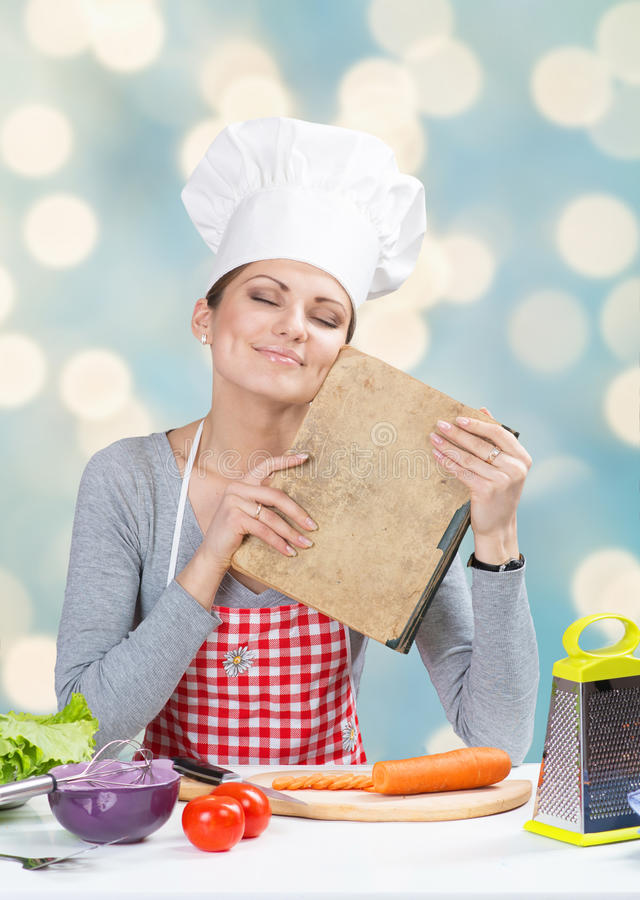 Woman in chef's hat with the old grandmother's cookbook. Portrait of smiling woman in chef's hat with the old grandmother's cookbook on abstract blue background stock photos