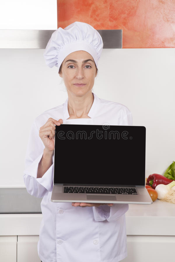 Woman chef showing blank laptop royalty free stock images