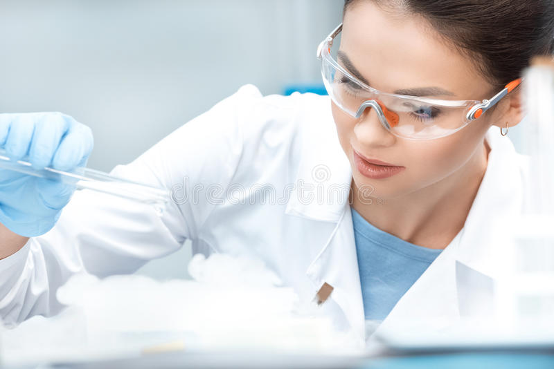 Woman chemist in protective goggles making experiment in laboratory. Young woman chemist in protective goggles making experiment in laboratory royalty free stock photo