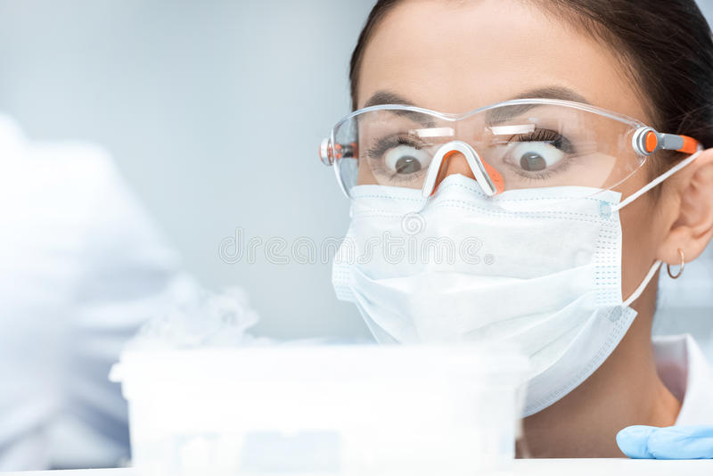 Woman chemist in protective goggles and mask making experiment in laboratory. Shocked woman chemist in protective goggles and mask making experiment in royalty free stock photo