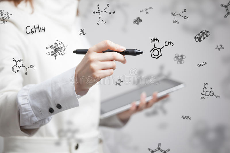 Woman chemist working with chemical formulas on grey background. stock photography