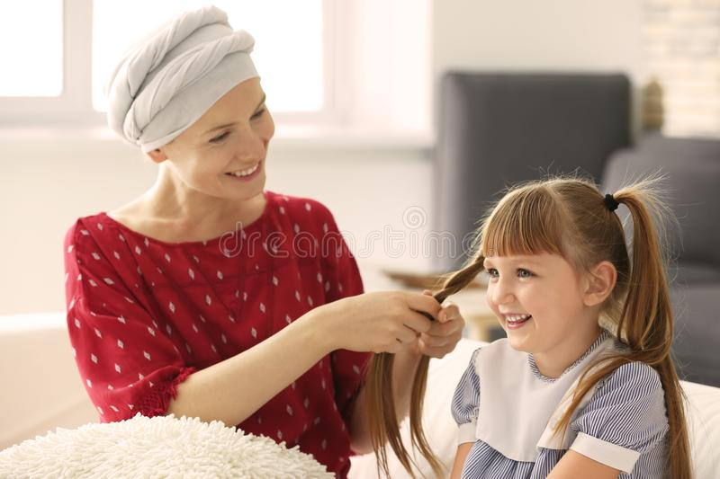 Woman after chemotherapy braiding her daughter's hair at home royalty free stock image