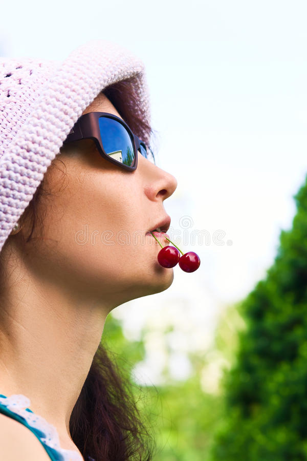 Woman with cherries. The woman in a hat and sunglasses with cherries in a mouth stock photography
