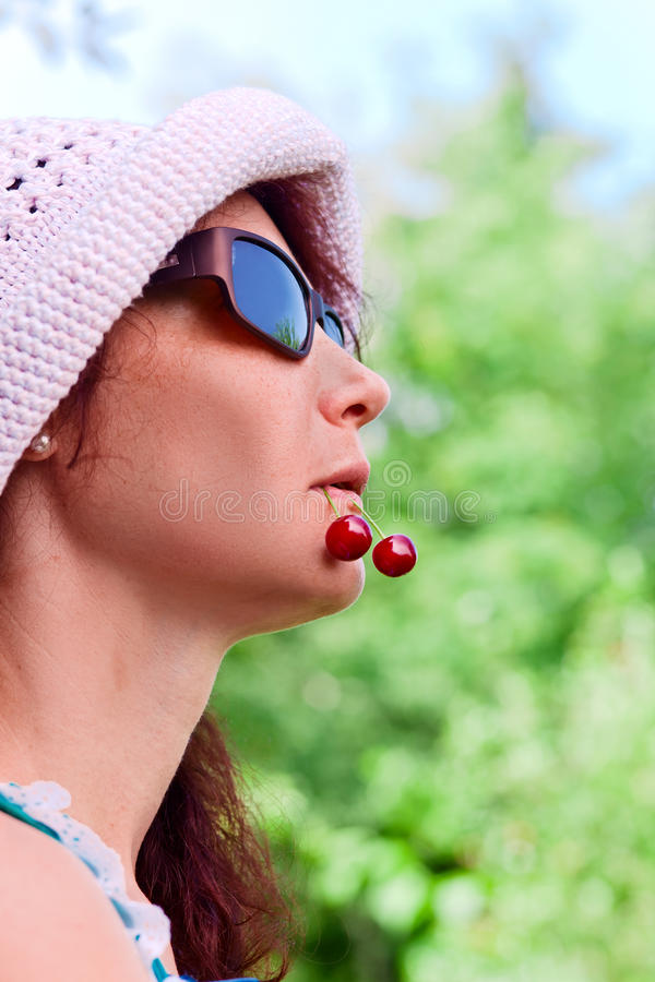 Woman with cherries. Woman of middle age with cherries in a mouth royalty free stock photo