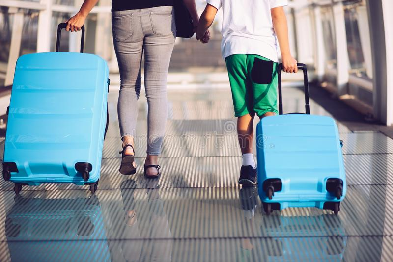 Woman and child with blue baggage suitcase on train station stock image