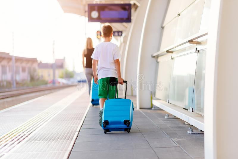 Woman and child with blue baggage suitcase on train station stock photography