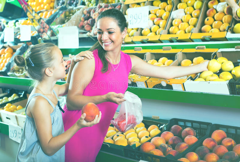 Woman with child buying fruits royalty free stock image
