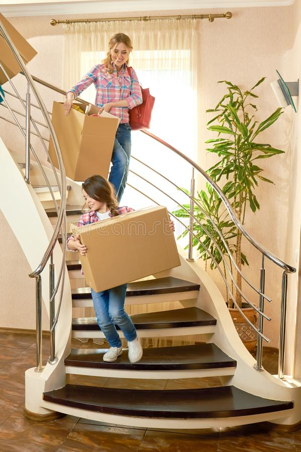 Woman and child carrying boxes. royalty free stock photography