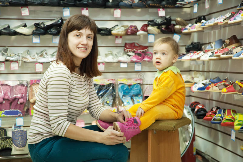 Woman with child chooses baby shoes stock photo