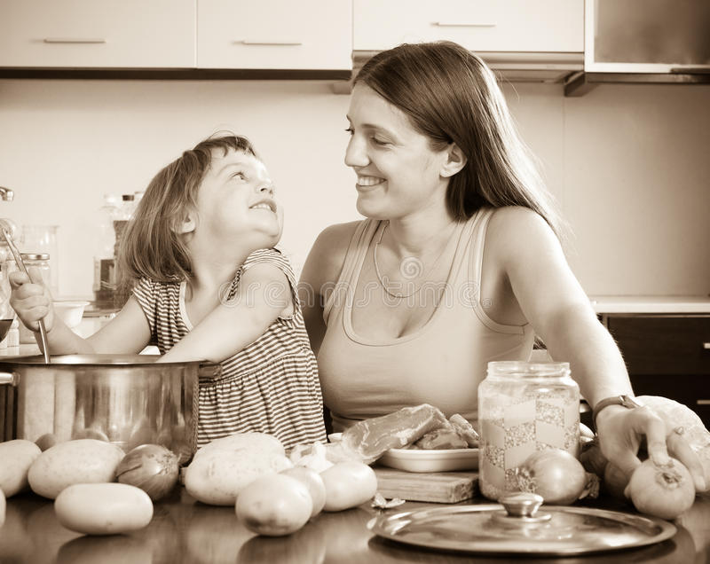 Woman with child cooking soup. Smiling women with child cooking soup royalty free stock photos