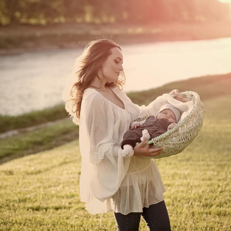 Woman with child in crib on sunny summer day. Mother hold baby son in basket on natural landscape. Mothers day concept. Family, love, trust. Vacation stock photos
