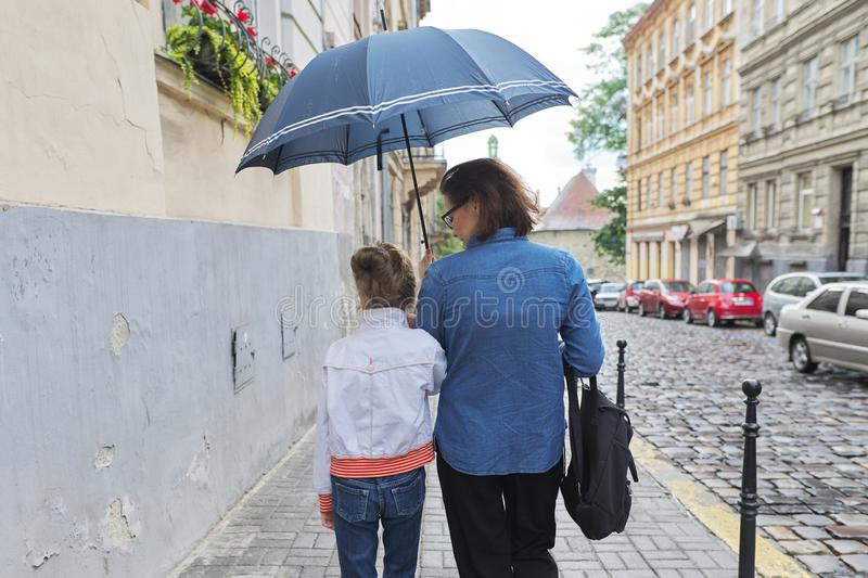 Woman with child girl walking under an umbrella in street. Rainy autumn weather in city, woman with child girl walking under an umbrella in street, rear view stock photo