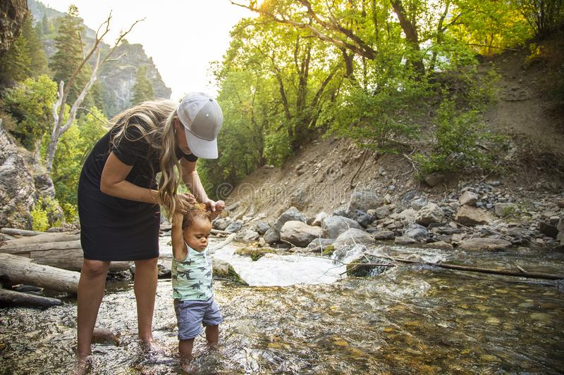 Woman and child hiking across a beautiful scenic mountain river. Walking in the mountain stream on a warm summer day together. lifestyle photo of a mother and royalty free stock photography