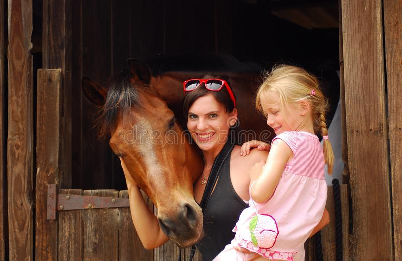 Woman and child with horse. An attractive young Caucasian women with a blond little girl hugging her brown horse in the stable royalty free stock images