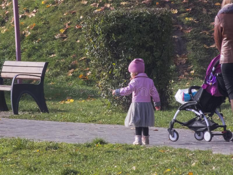 Woman with a child. Little girl walks in the autumn park. The girl is showing somewhere. Autumn time, autumn in the city stock images