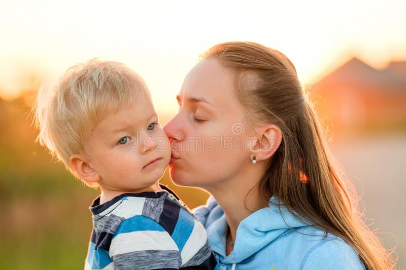 Woman and child outdoors at sunset. Mother kissing her son. royalty free stock photography