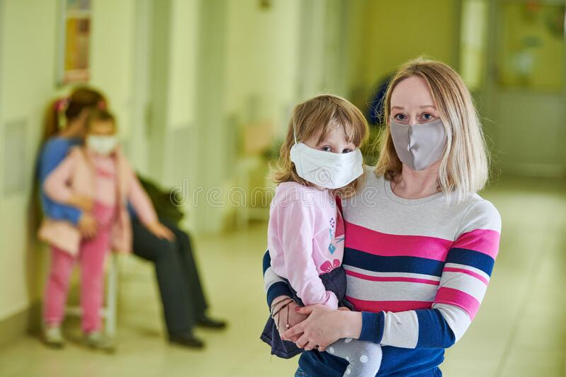 Woman and child in protective mask waiting doctor in hospital clinic hall at coronavirus epidemic stock photos