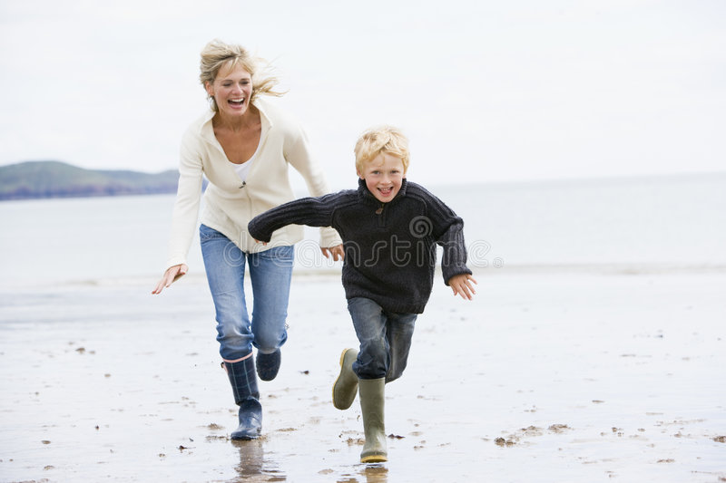 Woman and child running on beach. Smiling royalty free stock image