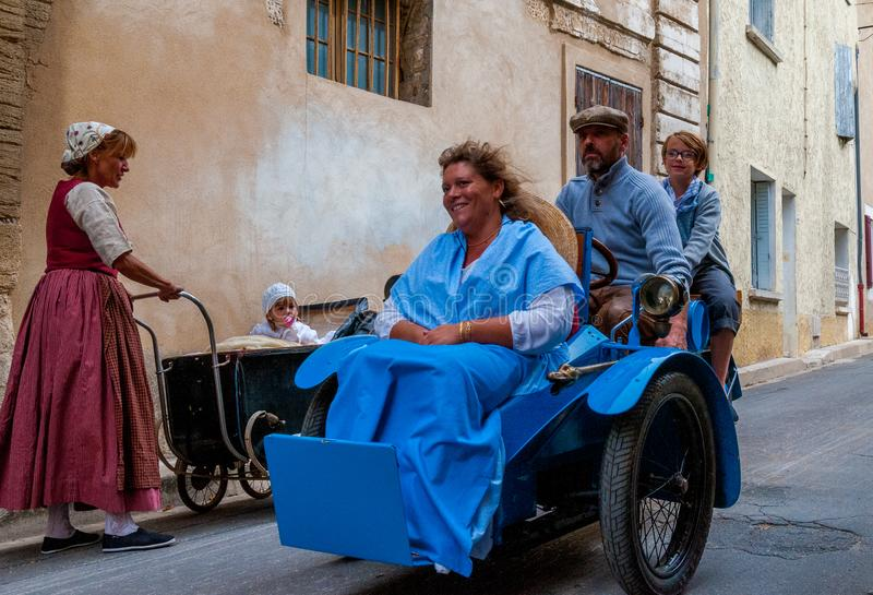 Woman with child in vintage pram  & family  in a vintage three wheeler ,dressed up in old fashioneed clothes   for heritage day stock photography
