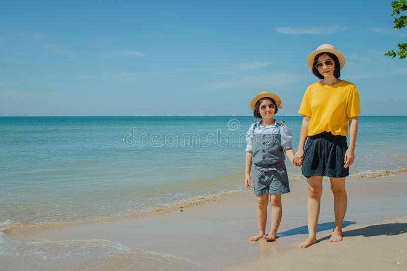 Woman and child walking on sand beach and they felling happiness. stock photography