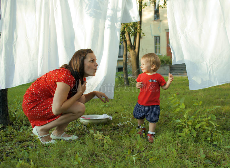 Woman with children in garden hanging laundry outside, playing with cute baby girl toddler, lifestyle people concept royalty free stock photography