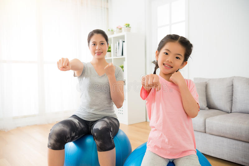 Woman and children hands gesture. As boxing and hit air with sitting on the fitness ball training balance and strength in the professional yoga class at gym stock photography