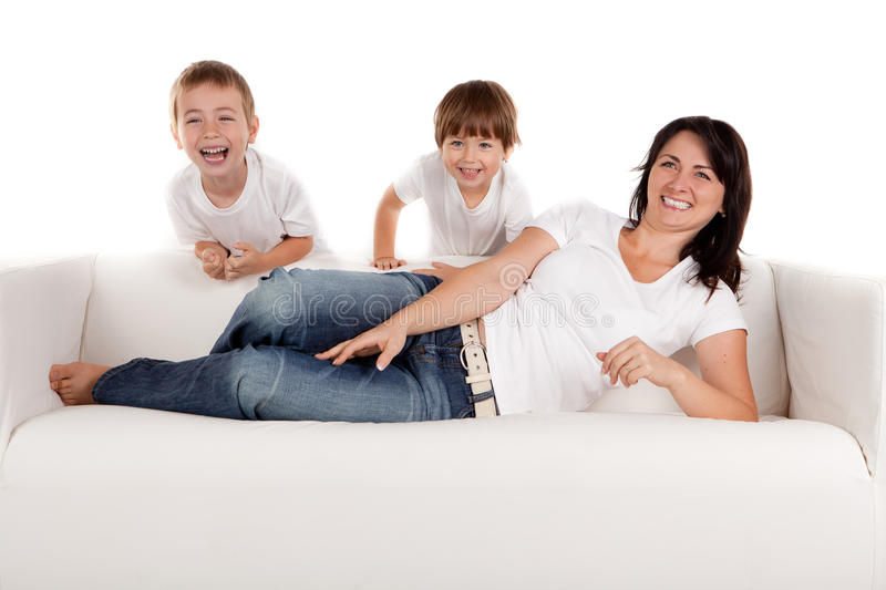 Woman and children playing. Women and children lying on a white sofa. White background stock photos