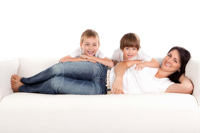 Woman and children playing. Women and children playing on a white sofa. White background stock image