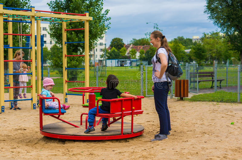 Woman and children by roundabout stock photos
