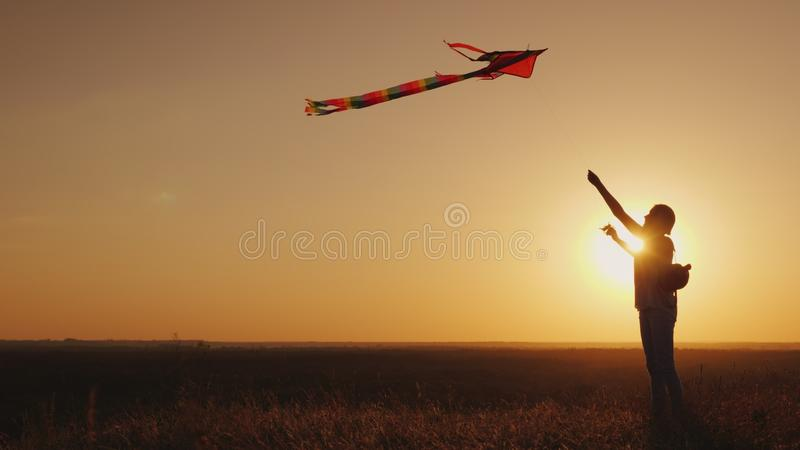 Woman With a children`s backpack behind her back runs a kite at sunset. Dream and return to childhood concept stock images