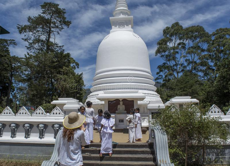 Woman and children in uniform on the stairs at white buddhist stupa building located in Nuwara Eliya town stock photography