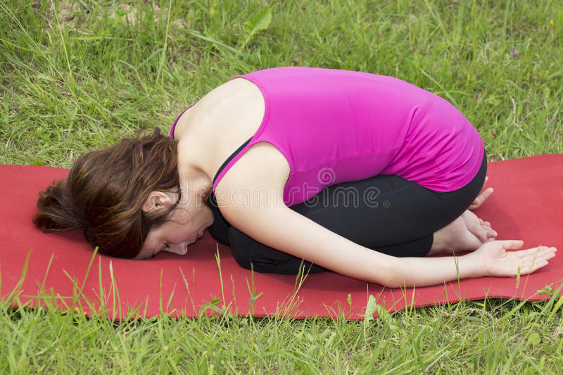 Woman in Childs pose during yoga outdoors royalty free stock photo