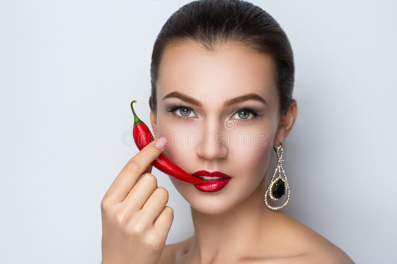Woman with chili peper. Young beautiful brunette woman (lady model woman actress). Luxury bright stylish look. Chic impressive appearance. Perfect face smoky stock image