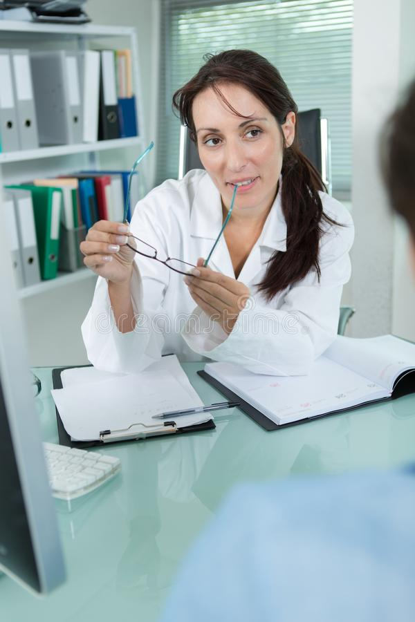 Woman choose glasses at doctor ophthalmologist optician royalty free stock photos