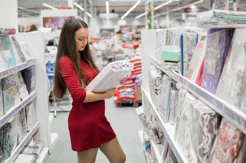Woman chooses bed linen and bed in the supermarket mall. Customer woman chooses bed linen and bed in the supermarket mall store. She is buying bedclothes royalty free stock photos