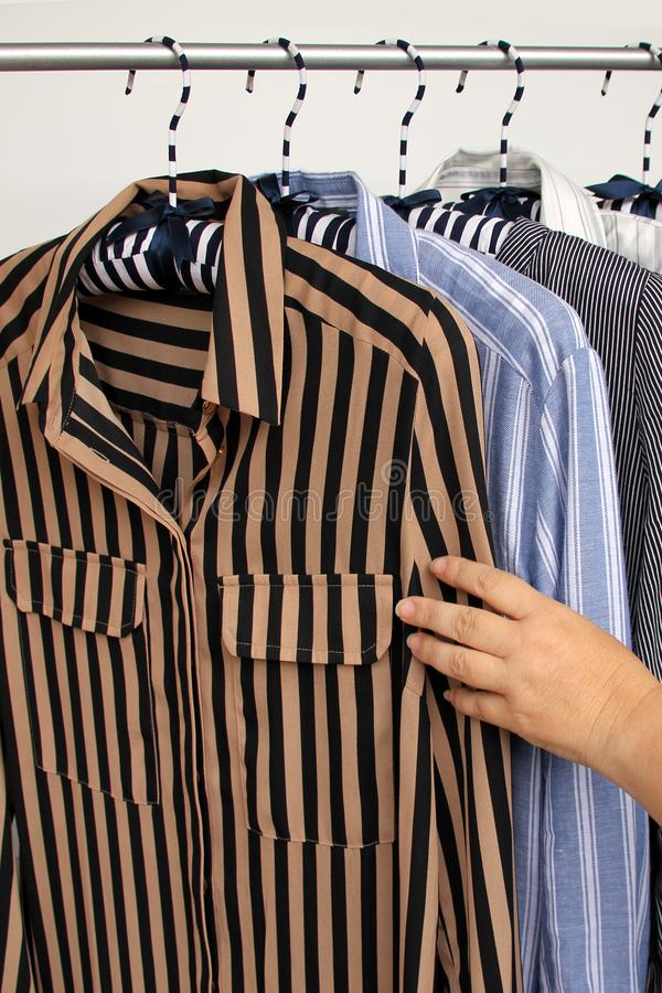 Woman chooses a blouse among women's clothes of different colors with stripes on hangers, a concept for fashion and shopping, royalty free stock photography