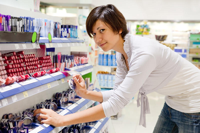 Woman chooses cosmetic at cosmetics shop stock images