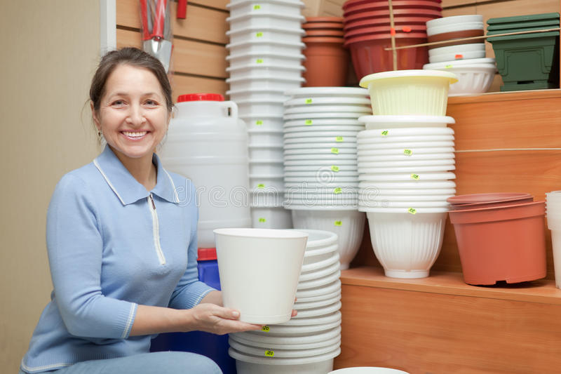 Woman chooses a flower pot. In the store for gardeners stock photos