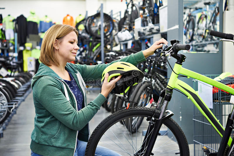 Woman chooses helmet for cycling in store stock images