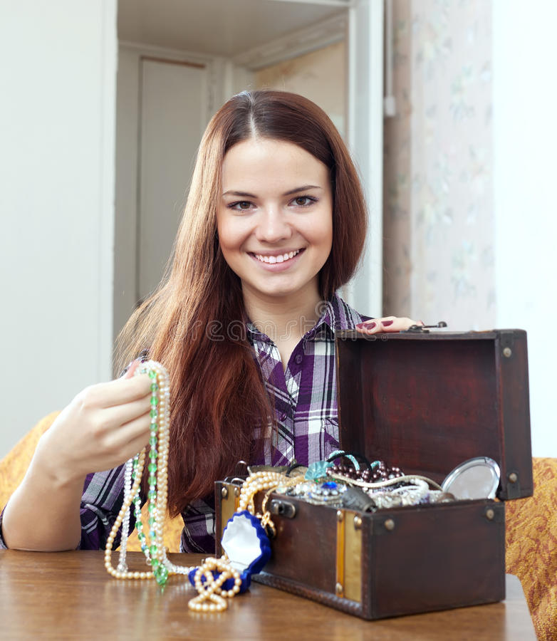 Woman chooses jewelry in treasure chest stock photos